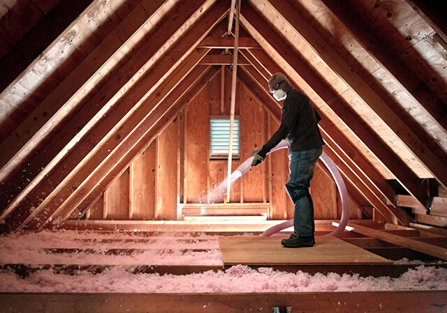 A picture of a home insulation contractor doing a blown in fiber glass home insulation